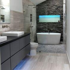 A beautiful modern bathroom featuring our Dusty Grey Pebbles and Vein Cut Limestone.
