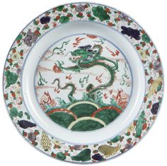 A Chinese Export Porcelain famille verte charger decorated with a dragon chasing the flaming pearl. Kangxi period. Asia. Decorated in the famille verte palette, with a dragon chasing the flaming pearl amongst the sea and separated by two carps.