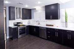 As seen on Brother Vs. Brother... Dark wood cabinetry, white subway tile backsplash and white marble countertops create a dramatic, timeless look in Drew's newly-renovated kitchen.