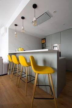 Cocina integrada con barra y taburetes mostaza. Encimera y frente de mármol. Reforma e interiorismo de vivienda para alquiler de lujo en Malasaña.  Proyecto de R de Room (www.rderoom.es)