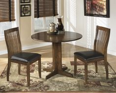 CONTEMPORARY BROWN DINETTE -  This great dinette features a round drop down table and beautifully shaped comb back chairs with leather look seating all in a warm brown finish.