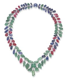 AN IMPRESSIVE ART DECO MULTI-GEM NECKLACE   Of flexible design, the tapering carved sapphire, ruby and emerald band, suspending a similarly-set fringe, enhanced by old European-cut diamond collet, to the central cabochon emerald and sapphire clasp, mounted in white gold, circa 1930, 17 1/8 ins.
