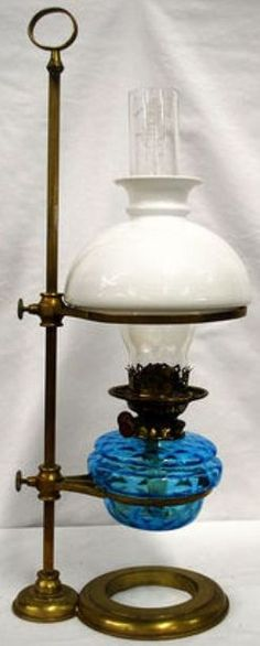 lighting, America, An adjustable height [holder, oil] lamp, blue diamond font, milk glass shade, [brass frame with finger loop]. circa 1876-1925
