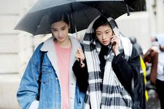 Models Dylan Xue and Chu Wong, in the rain after Acne Studios, on Day 5 of Paris Fashion Week Ready to Wear Autumn/Winter 2017/18.