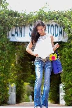 White lace top, flare jeans and blue bag.