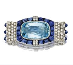 AQUAMARINE, SAPPHIRE AND DIAMOND BROOCH, CARTIER, PARIS, CIRCA 1930.  Centering a cushion-shaped aquamarine weighing approximately 13.90 carats, bordered by buff-top calibré-cut sapphires and pavé-set single-cut and old European-cut diamonds weighing approximately 1.50 carats, the sides accented with sugarloaf cabochon sapphires, mounted in platinum, signed Cartier, Paris, numbered 6238B, assay marks.