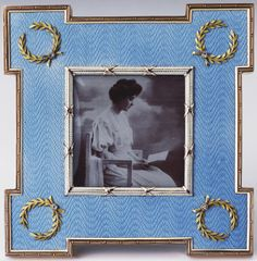 Fabergé square strut frame of two-colour gold with projecting corners, pale blue moiré guilloché enamel borders with brilliant diamonds set in laurel wreaths at each corner, tied bezel inset with photograph of Princess Patricia of Connaught. Mark of Karl Armfelt, c. 1905. Bought by Tsar Nicholas II and Tsarina Alexandra Feodorovna, 14 July 1907 (175 roubles); by whom given to King Edward VII and Queen Alexandra.