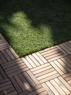 Wood parquet tile and artificial grass in enclosed patio. Parquetry- inlaid wooden flooring in geometric forms or designs. No weed wacker or lawnmower required.