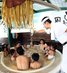 Bathing in a tub of ramen soup in Japan: Ichiro Furuya, founder & cook of a popular noodle store 'Nantsuttei' throws the imitation noodles bath agent into 'soup noodle spa' at the Hakone Yunessun Spa