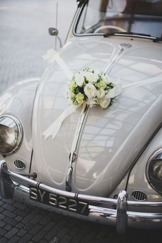 Simple and rustic wedding car flowers on a vintage wedding car. See the full…