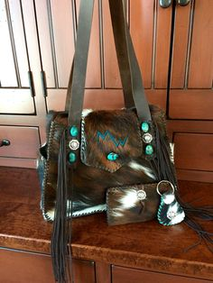 The cowhide Bonnie Bag with the owners brand in turquoise suede and exterior side pockets, with matching checkbook cover and key fob. gowestdesigns.us