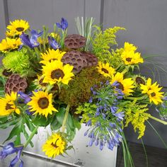 Floral Design by Lilies White. Casket spray featuring sunflowers, dried pods, fresh moss, iris and agapanthus.