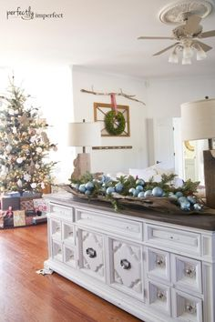 Perfectly Imperfect Christmas Home Tour.   Love the huge piece of drift wood filled with the greenery and ornaments.