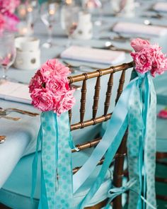 Rose and Ribbon Swag Swags of blue ribbon adorned this brides chair, which also boasted vibrant pink hybrid roses.