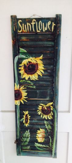 Painted sunflowers on an old shutter with original green paint.