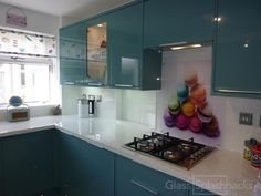 Rainbow Macaroons Printed Glass Splashback in a 1950s style kitchen. We love the coordination of this scheme! The clients stunning units were installed long before the glass splashback was bought, however we're delighted to say the splashback has certainly done them justice. The overall scheme is bright, and fun.
