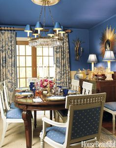 This dining room, designed by Eric Lysdahl, features dark blue walls and a dark blue ceiling, which allows the white elements to pop while creating a rich, velvety background for gilded picture and mirror frames.