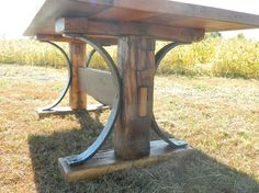 A neat old farm table. Original hand hewn uprights from an old granary. Amazing workmanship from a real blacksmith hammering out 3/4in x 3in curves to bring the table together. Wonderful reclaimed white oak top full of character and variation. This table was one of the first pieces that Kevin Coffel from Antique Woodworks and Wyatt