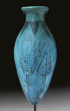 AN EGYPTIAN FAIENCE LOTUS VESSEL   New Kingdom, Dynasty XVIII,  1550-1307 B.C.  Blue in color, the piriform bottle with off-set disk rim, the details in black glaze, with joined triangles on the neck, alternating opened lotus flowers and buds on the body  6¼ in. (15.9 cm.) high