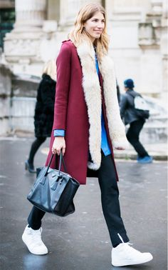 Style maven Veronika Heilbrunner in a fur-collar maroon coat, slouchy black trousers, and sneakers.