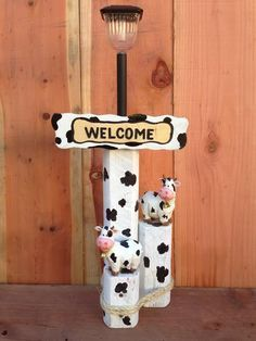 Solar Light Designs are handcrafted from landscaping timber for weather durability and includes a custom-painted sign, solar light and cow figurines.