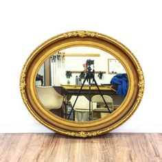 This oval mirror is featured in a solid wood with a shiny gold finish. This accent mirror is in good condition with intricate carved trim, rounded edges and floral accents. Perfect for decorating any wall! #americantraditional #decor #mirror #sandiegovintage #vintagefurniture