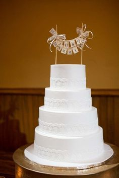 A white wedding cake with a rustic bunting topper and lace border for a rustic wedding reception.