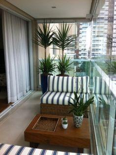 Varanda com dois sofás pequenos, mesa de centro em madeira, decoração com plantas. Fechamento de vidro. Arquiteta Danyela Corrêa