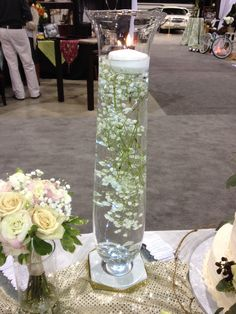 babys breath submerged in water w/ floating candle on top. I'd like to see this with pearls or gold or silver hypericum berries on gold or silver wire worked in.