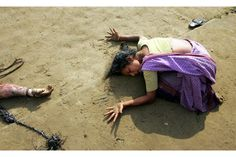 An Indian woman mourns the death of her relative (L) who was killed in the tsunami in Cuddalore, some 180 km (112 miles) south of the southern Indian city of Madras in this December 28, 2004 file photo. The South East Asia Tsunami killed 230,000 people in 14 countries. It was one of the deadliest natural disasters in recorded history.  Indonesia was the hardest-hit country, followed by Sri Lanka, India, and Thailand.