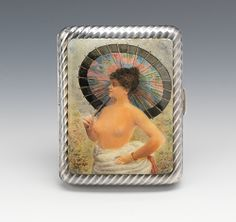A Continental Silver & Enamel Cigarette Case   Ribbed silver case with hinged cover having polychrome enamel painting of woman with a parasol, unsigned, with faint touch marks on case. The interior is gilt and with old elastic.