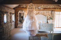 The bride's Martina Liana gown hangs from a beam in Jasmine Cottage #upwalthambarns