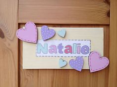 Handcrafted personalised children's plaque in pastel colours.  Embellished with painted wooden hearts