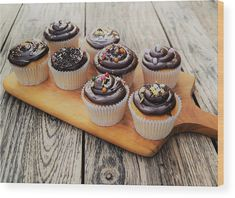 Chocolate Cupcakes Rustic Style wood print. Delicious decorated chocolate cupcakes on a handled cutting board with rustic wood table background. Cupcake art for kitchen, bakery, cafe or gift. Exclusive design available only at Fine Art America and Pixels.com. https://andrea-rea.pixels.com/