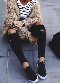 Beige knit cardigan over striped tee and black jeans.