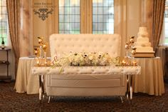 A table for two fit for a King and Queen! Custom table and sofa, complete with gold Mr. & Mrs. sign, and an arrangement filled with white floral. Including white anemone, ranunculus, hydrangea, orchids, and roses  #adamleffelproductions #luxewedding #custom #white #wedding #flowers #njwedding