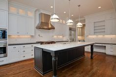 Three Restoration Hardware Classic Clemson Pendants illuminate a black distressed kitchen island ...