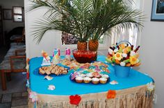 Here's how our Lilo & Stitch party table turned out with the ideas pinned on this board. L-R: Pudge's PB sandwiches, pineapple cupcakes with coconut flavored cloud frosting and cocktail umbrellas, punch with the flower ice cubes, crushed graham crackers (sand) with Nutter Butter sandals and the pineapple palm trees (for some reason the preview doesn't load, but you can click the image to see it large!)