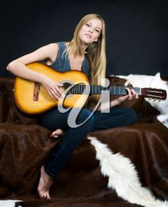 Royalty Free Photo of a Young Woman Playing Guitar