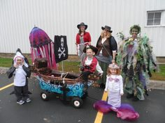 Pirate theme Halloween group costumes. Cardboard ship on wagon, shark costume from felt, 3 pirate costumes from basic pieces, a mermaid, a jellyfish made from an umbrella and fabric scraps,and a sea monster made from plastic and bubble wrap.