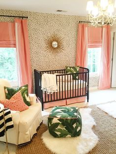 A coral and gold Palm Beach inspired nursery featuring a black and cream Dalmatian print wallpaper accent wall and green palm accents.