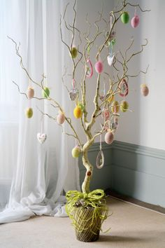 Arbol de Pascua sin hojas ni flores, decorado con nuevos y corazones en un mini pote cubierto y enlazado con hilos de rafia. Yo hice uno parecido.