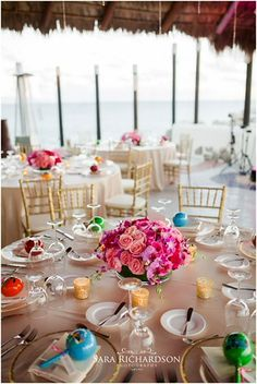 Gold Rim Chargers with beautiful Centerpieces in the middle of Roses & Cymbidium Orchids with Wedding Favor Maraca... #Colors #Wedding #BestDestinationWeddings #DestinationWeddings #Love #CaboWeddingServices #CaboWeddings #LosCabosWeddingCoordinators #SunsetMonaLisa #CaboSanLucas #LosCabos #Mexico