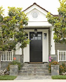 Black front door, white trim, greige house, stone steps and porch