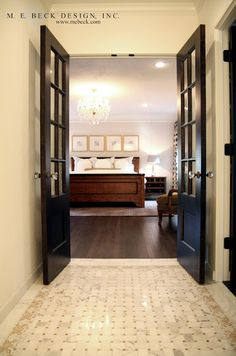 Double dark wood doors leading to the master with glass panes and crystal door knobs