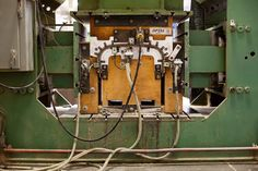 The press machine that turns a bundle of veneer sheets into the back panel for an Eames lounge.