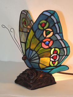 "This beautifully colored stained glass with copper foil butterfly Memory Lamp offers warm reflections of colorful light. Hues of blue, green, red, orange and white make up the stunning wings that sit on the brushed bronze base of a bed of roses. With all of our 'Gifts of Light' occasion cards, gift wrapping, and bulbs are always included. Measures 6""w x 10""h. You can view all of our gorgeous Memory Lamps and occasion cards on our website: http://www.memorylampsofbeverly.com"