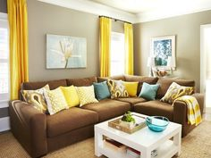 Stylish Condo Living : Decorating : HGTV - The sectional, which a local company custom-made to fit the space. It's an upgrade from the leather castoff couch in their old house, and the canvas cushions and L-shape allow for comfy TV watching. Living Room Decor Brown Couch, Paint Colors For Living Room, New Living Room, Living Room Furniture, Teal Couch, Living Room Yellow, Brown Furniture Decor, Tan Sofa, Brown Decor