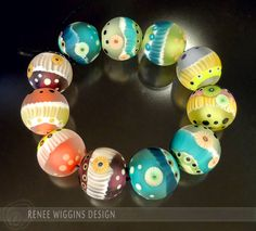 """Hula Beads"". Fun, bright colored etched beads with a mini ""hula skirt"" surface adornment with raised dots and handmade murrini. They measure about 18mm diameter. RWD 2015."