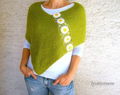 This hand knit green poncho is embellished with crochet white daisy flowers.